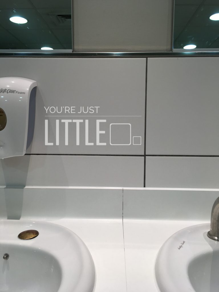 You're Just Little - Toilet mirror in Marks and Spencer - perspective standing in front of wash basins and tiles straight ahead, the mirror is above my head and I cannot see my reflection