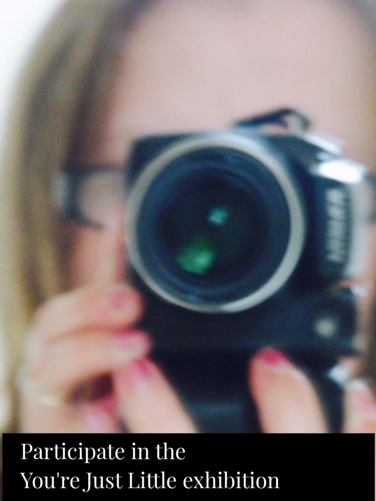 Blurred photo of Hello Little Lady holding a camera in mirror with the blog title - Participate in the 'You're Just Little' photographic exhibition