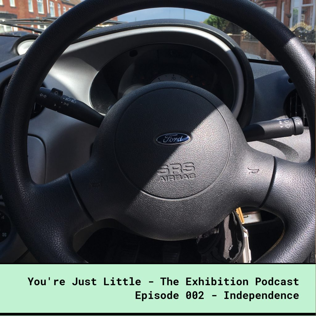 You're Just Little - The Exhibition Podcast - Episode 002 - Independence. Photo by a dwarf person sitting in the driver's seat of an unadapted car.